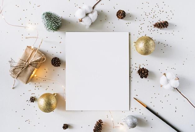 크리스마스 축제 장식 및 흰색 rustick 벽에 인사말 카드. 빛나는 황금 공 빈 종이, 선물 및 coton 분기. 새 해 평면 누워, 평면도, 복사 공간.