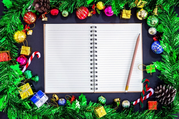 Christmas festive decorations with empty notebook and pencil on black paper background, ne