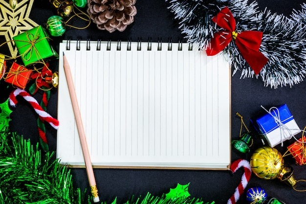 Christmas festive decorations with empty notebook and pencil on black paper background