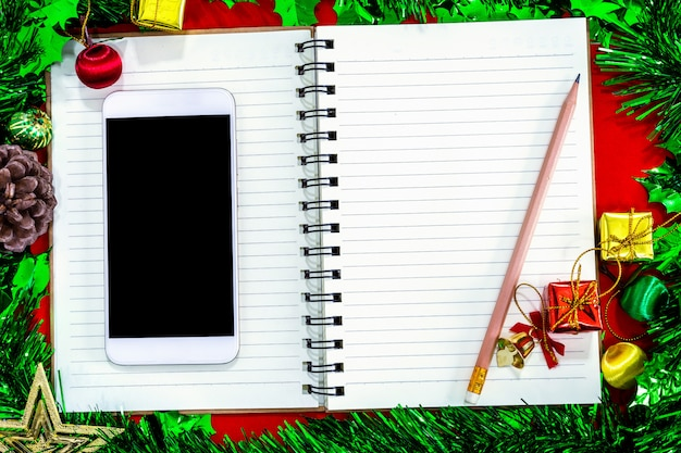 Christmas festive decorations with empty smartphone,notebook and pencil on red paper backg