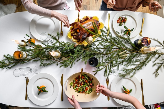 Christmas festive dinner. delicious traditional holiday meal and hands of people eating them. decorated table with tasty dishes. flat ley. white table