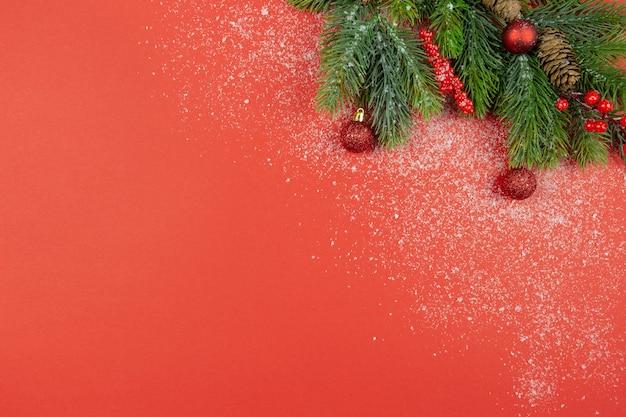 クリスマスのお祝いの赤い装飾と赤い背景に雪とモミの木の枝