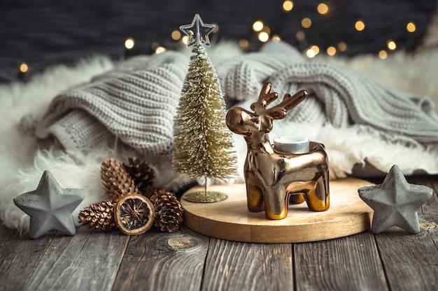 おもちゃの鹿、黄金色のライトとキャンドルでぼやけたテーブルでクリスマスお祝いテーブル