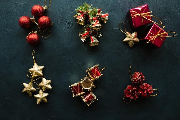 Ассортимент рождественских праздничных игрушек на темной стене. атрибуты зимних праздников