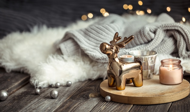 Christmas festive wall with toy deer, blurred wall with golden lights and candles, festive wall on wooden deck table