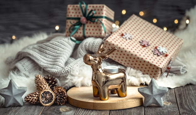 Christmas festive wall with toy deer with a gift box and christmas tree, blurred wall with golden lights on wooden deck table