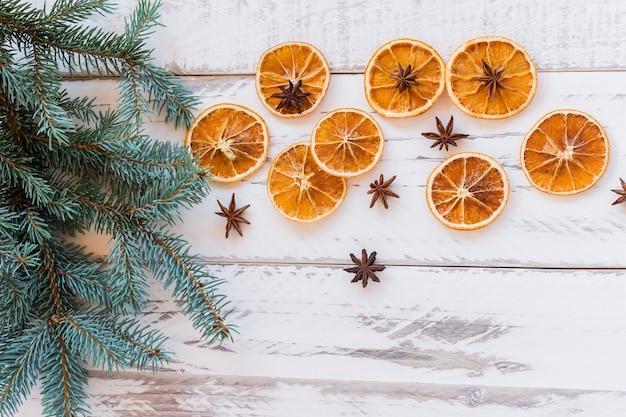 素朴な木製のテーブルにモミの木の枝、乾燥したオレンジとアニスの星とクリスマスの祝祭の背景。コピースペースのある上面図