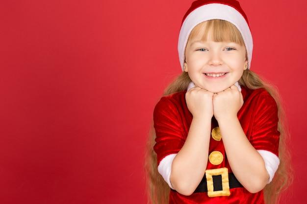 크리스마스 열병. 빨간색 스튜디오에서 포즈 크리스마스 복장에 작은 사랑스러운 소녀의 가로 세로
