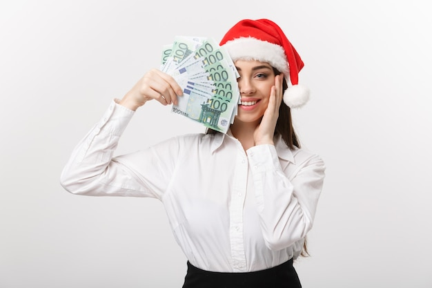 Christmas and finance concept  young business woman showing money closing her face with surprise expression