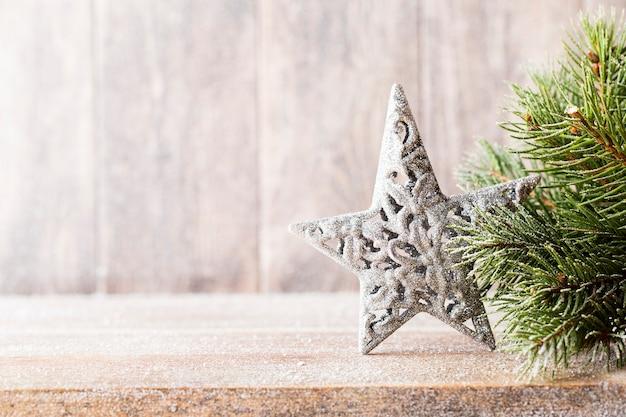 木製の背景に、クリスマスのモミの枝と装飾。