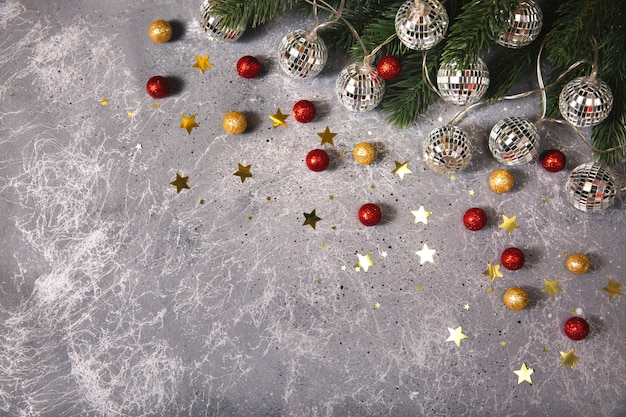 Рождественская еловая ветка с декоративными гирляндами, светящимися светом на сером фоне с золотыми и красными шарами и звездами. плоская планировка