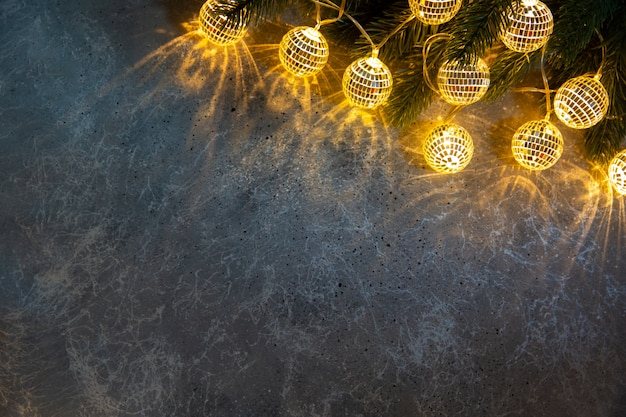 Рождественская еловая ветвь с декоративными гирляндами, светящимися светом на сером фоне текстуры. плоская планировка