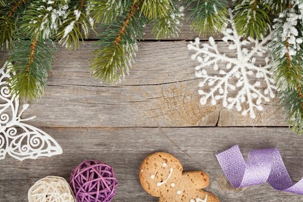 나무 판자 배경에 눈으로 덮인 크리스마스 전나무와 장식