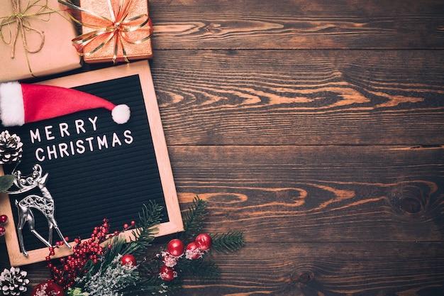 木の板に文字板メリークリスマスとクリスマスモミの木の枝