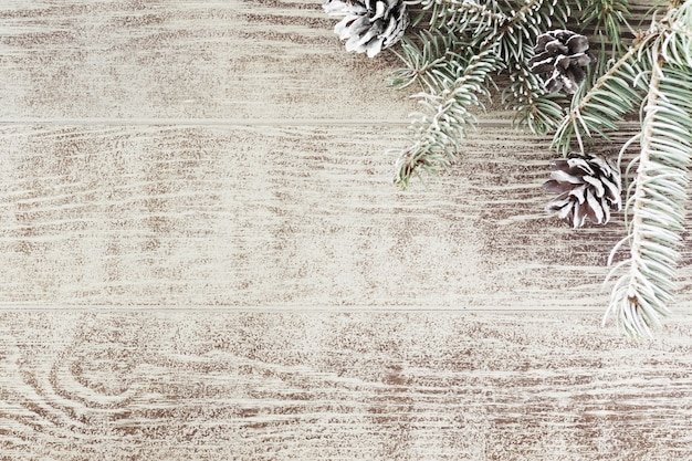 Christmas fir tree branch with pine cones on white rustic wooden table. winter background with copy space. top view. flat lay