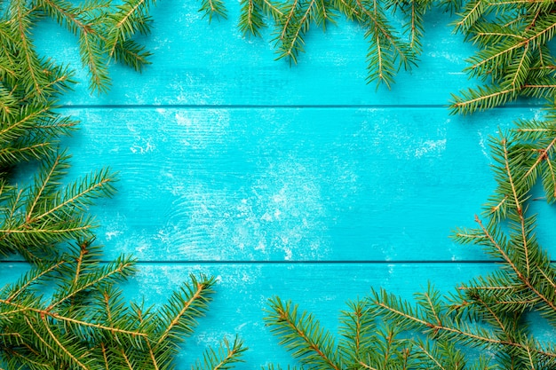 Christmas fir tree branches on blue rustic wooden board with copy space