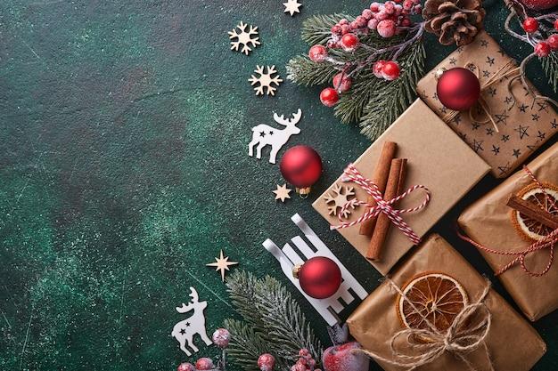 크리스마스 전나무 나뭇가지, 크리스마스 공, 선물 상자, 나무 눈송이, 그리고 크리스마스 인사말을 위한 녹색 콘크리트 돌 배경의 별들. 복사 공간이 있는 상위 뷰입니다. 크리스마스 인사말 카드입니다.