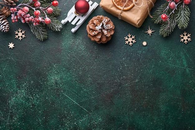 クリスマスのモミの木の枝、クリスマスボール、ギフトボックス、木製の雪片、クリスマスの挨拶のための緑のコンクリートの石の背景に星。コピースペースのある上面図。クリスマスのグリーティングカード。