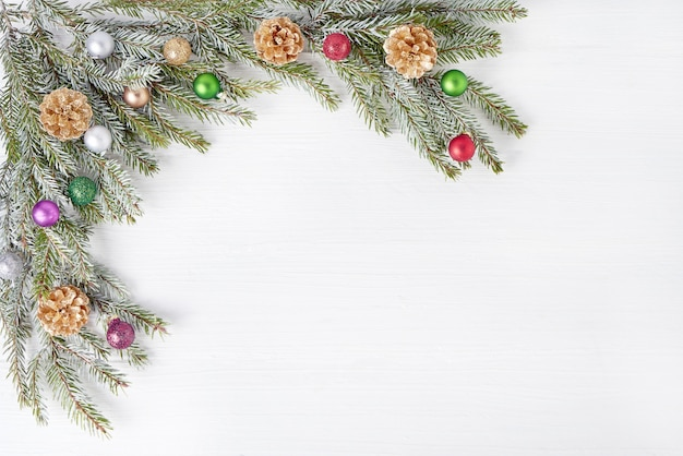 Christmas fir tree branches decorated with gold cones on white wooden background. copyspace