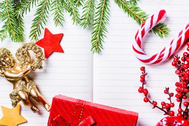 クリスマスのモミの木の枝、装飾、天使、キャンディケイン、冷凍の赤い果実、星、ノートブックのギフトボックスフレーム