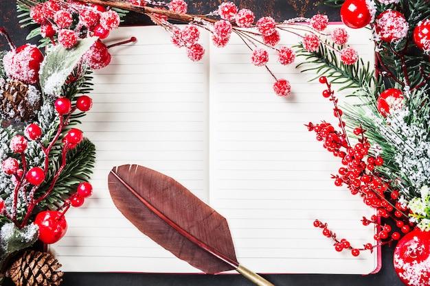 クリスマスのモミの木の枝、装飾、キャンディー、冷凍の赤い果実、ノートブックの古いビンテージ羽ペンフレームとコーン