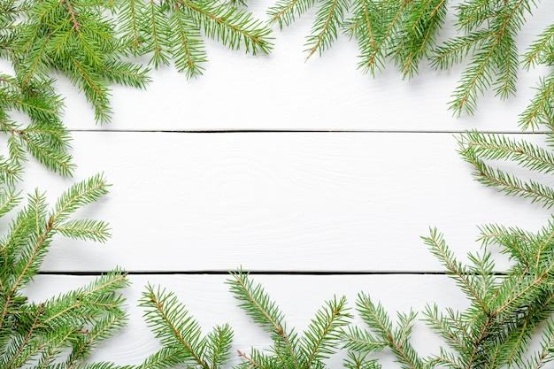 コピースペースを持つ白い素朴な木の板にクリスマスのモミの木の枝