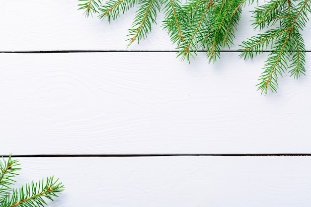 Christmas fir tree branches on white rustic wooden board with copy space