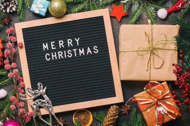 メリークリスマスという言葉が書かれた文字板の近くにギフトボックスが付いたクリスマスモミの木の枝。