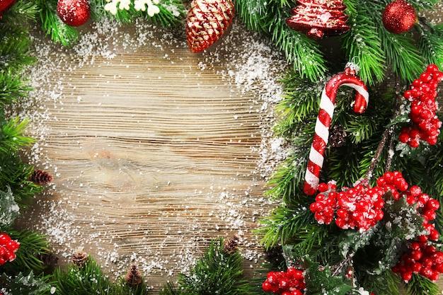 Рождественские еловые ветки с рябиной и игрушками на деревянном столе