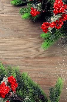 Рождественские еловые ветки с рябиной на деревянном столе