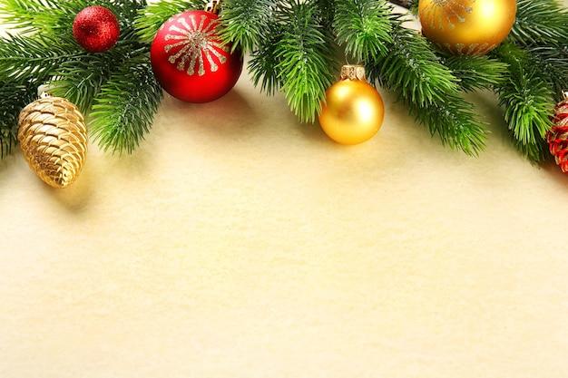 紙の背景におもちゃでクリスマスのモミの木の枝