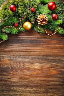 Рождественские еловые ветки с игрушками на деревянном столе