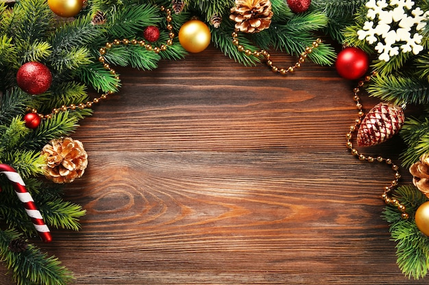 木製のテーブルの上のおもちゃとクリスマスのモミの木の枝