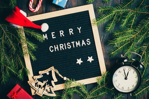 Christmas fir tree branches with vintage alarm clock and giftboxes on rustic wooden board near letter board with words merry christmas.