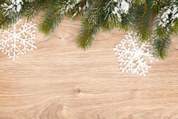 나무 판자 배경에 눈으로 덮인 크리스마스 전나무