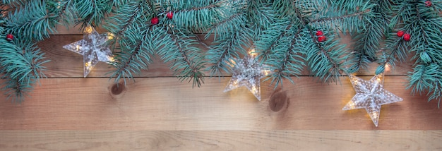 Christmas fir tree and garland on wooden table, banner