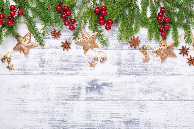 Christmas fir tree and gifts on wooden background.