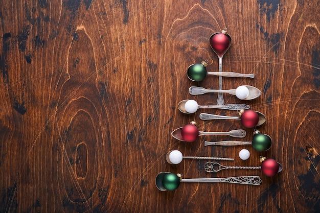 나무 배경에 빨간색과 녹색 크리스마스 공이 있는 오래된 숟가락이나 칼붙이로 만든 크리스마스 전나무와 크리스마스 인사를 위한 공간을 복사합니다. 크리스마스 인사말 카드입니다. 복사 공간이 있는 상위 뷰입니다.