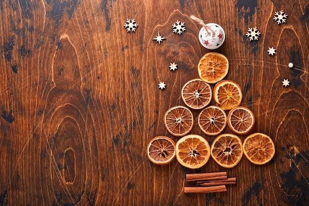 모양의 계피와 마른 오렌지 조각으로 만든 크리스마스 전나무와 크리스마스 인사를 위해 나무 배경에 빨간색과 녹색 크리스마스 공이 있습니다. 복사 공간이 있는 상위 뷰입니다.