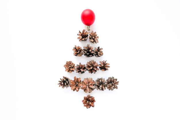 Christmas fir tree made of pine cones and redball on white background.