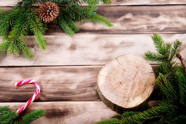 Christmas fir tree on natural wood with candy and round wooden cut.