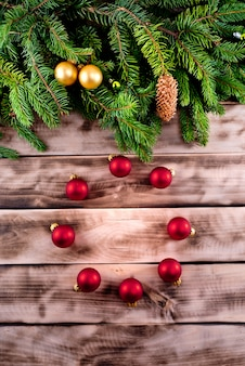 Christmas fir tree on natural wooden background with red balls.