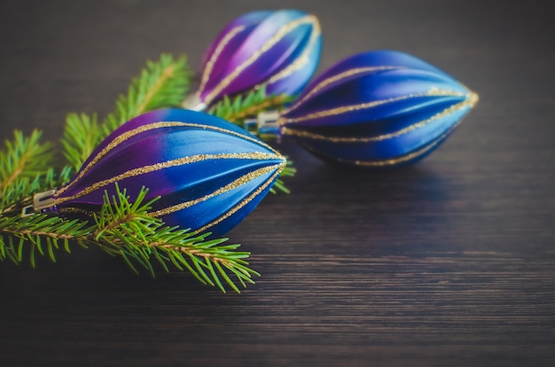 Christmas fir tree and purple decoration on wooden board.