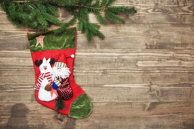 Christmas fir tree, red christmas socks on wooden background.