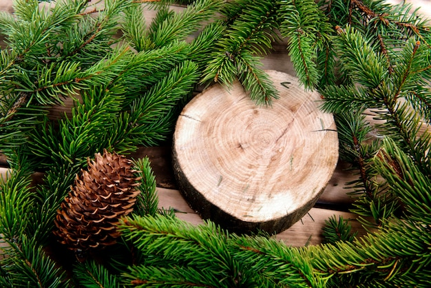 Christmas fir tree and round wooden cut on natural wood