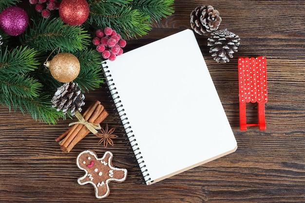 Рождественская елка с украшением и пустой запиской на коричневой деревянной доске
