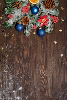 Christmas fir tree with decoration on dark wooden board. with copy space for text.