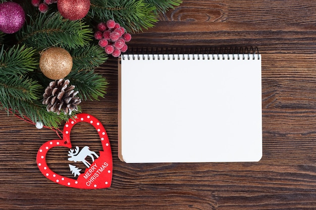Christmas fir tree with decoration and empty note on brown wooden board
