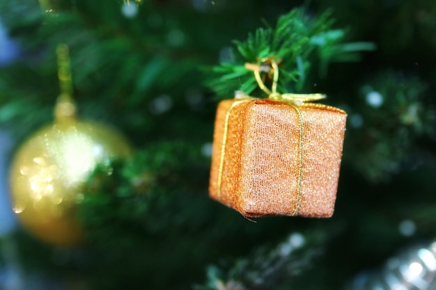 Christmas fir tree with decoration, old rose gift box. selective focus.
