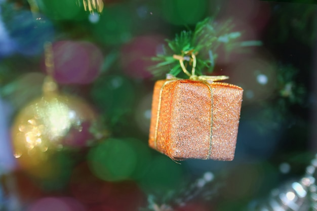 Christmas fir tree with decoration, old rose gift box with bokeh.